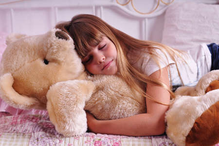 Portrait of sleeping girl with toy plush bear photo