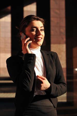 ourdoor: Business woman ourdoor portrait speaks mobile phone looking at camera