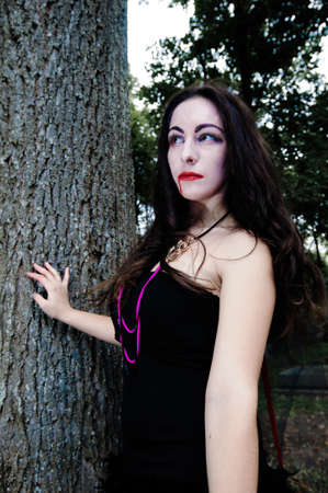 scaring: Pretty vampire near tree with blood Stock Photo