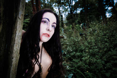 Vampire gilr portrait near tree on cemetery photo