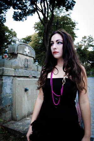Pretty vampire near charnel house walking through graveyard photo