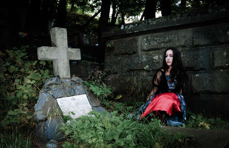 crypt: Pretty vampire sits  near grave and looking to concrete cross