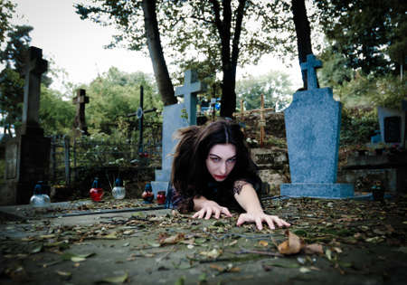 Scary vampire girl with white face and blood coming and looking at camera photo