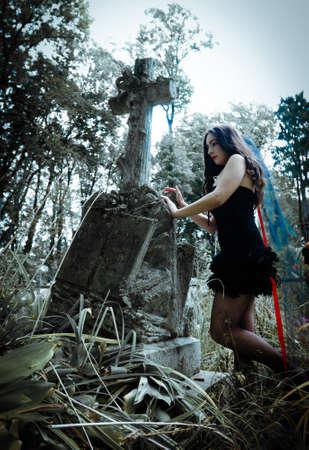 Pretty vampire near tree with blood photo