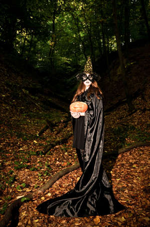 arrogant teen: Smiling pretty young witch in forest stands in black mantle and holding pumpkin