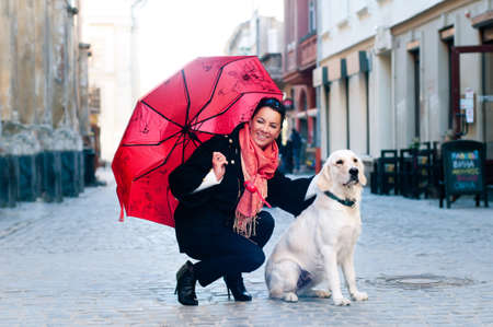 Pretty woman sits in old city with dog and looking at camera photo