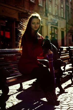 back lighting: Pretty girl sitting on bench on Lviv central street Stock Photo