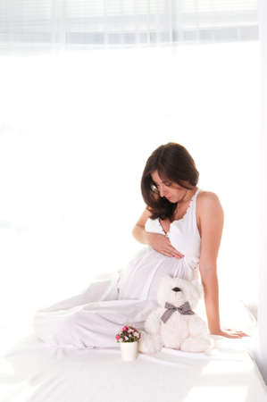 Pregnant woman portrait in white dress with bucket of flowers looking to her belly photo