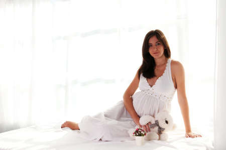 Pregnant woman portrait with bear toy sits and looking at camera photo