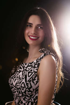 back lighting: Portrait of beautiful woman on dark background with back lighting