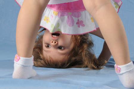 rapturous: Cute little girl upside down standing on her head and looking surprised