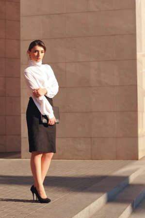 Business woman portrait outdoor stands and looking at camera photo