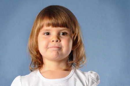 two years: Closeup portrait of white two years girl looking directly at camera and making faces. She is blond and wear white t-shirt, standing on blue background at studio.