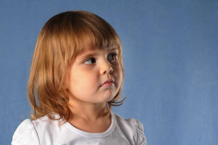 looking aside: Small white girl two years old closeup portrait in studio on blue background looking aside thinkfully