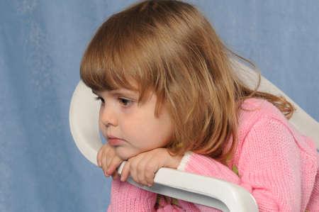 sadly: Piccolo due anni vecchia gilr si siede sulla sedia di plastica bianca e purtroppo ha messo la testa sulle sue mani. Guardando da parte e pensare. Lei � bella e ha i capelli biondi, indossare rosa maglione lavorato a maglia. Archivio Fotografico