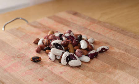 kidney beans: Heap of kidney beans on wooden kitchen board Stock Photo