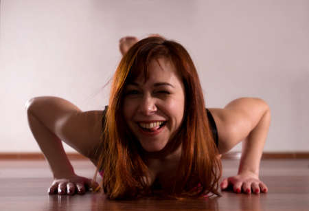 Woman thirty ears push-ups on wooden floor before training of pole dance