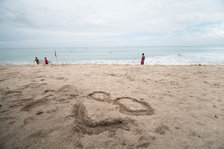 happy smile face drawing on the sand in beach