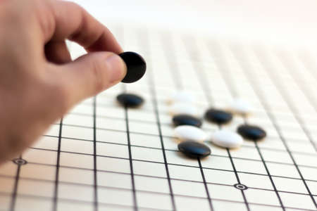 Traditional Chinese Board Game - Go (Male hand playing his move)