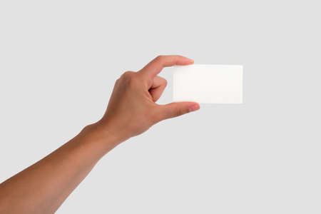 Female Hand Holding a Blank Business Card  Isolated on light grey background