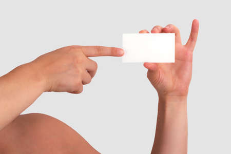 Woman Holding Blank Business Card and pointing it with her other hand  photo