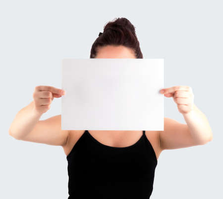 Young Casual Woman Holding a Blank Signboard - Paper with her two hands, isolated on light grey background   No face shown