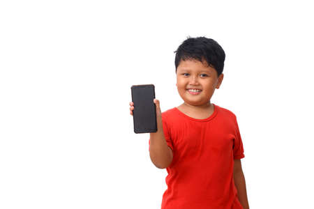 Asian boy in red shirt standing while showing his blank smartphone screen. Isolated on white background with copy space