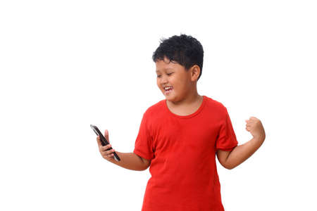 Asian boy in red shirt standing and happy while looking on smartphone screen. Isolated on white background with copy space