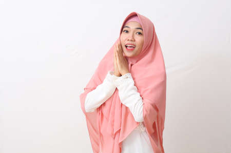 A portrait of surprised Asian Muslim Woman wearing a veil or hijab while standing. Isolated on white background with copy space Stock Photo