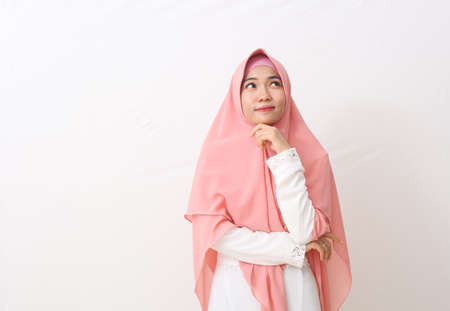 A portrait of happy asian muslim woman wearing a veil or hijab looking something on blank space while hand is on the chin. Isolated on white background with copy space