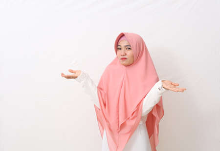 A portrait of asian muslim woman wearing a veil or hijab shrugging shoulder, denial or I don't know gesture. Isolated on white background with copy space