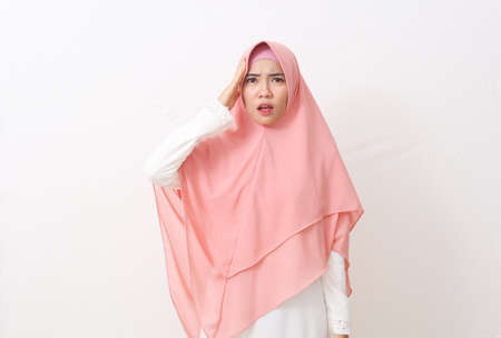A portrait of shocked panic asian muslim woman wearing a veil or hijab holding hands on head. Isolated on white background with copy space