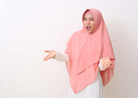 Asian muslim woman in a pink veil or hijab and white dress feels crazy and mad shouting and yelling with aggressive expression and arms raised. Frustration concept. White background with copy space