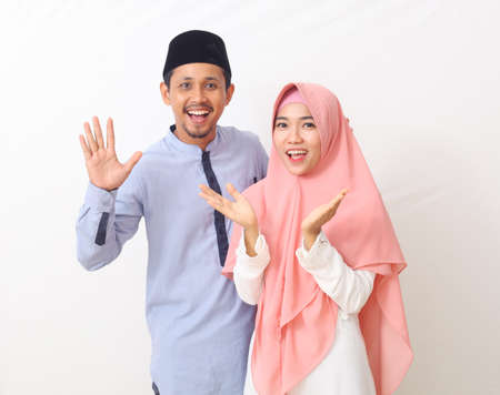 A portrait of a happy Muslim couple surprised by a good news. Isolated on white background.