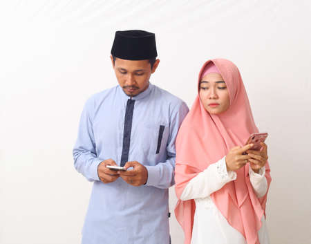 Portrait of asian muslim couple using smartphones. A woman peeked at the man's cellphone. Isolated on white background