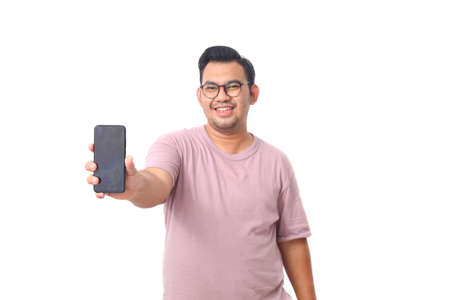 Portrait of happy asian male wearing glasses and purple shirt standing while showing his blank screen smartphone. Isolated on white
