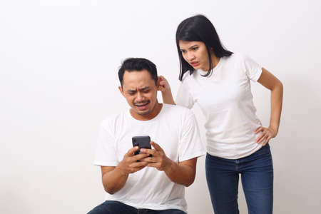 Angry young woman pulling ear lobe of surprised shocked in pain hurting funny man. cute girl showing pulls ear after looking a boyfriend's smartphone