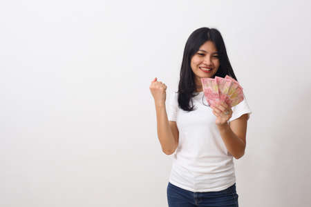 Happy asian girl holds an Indonesian money while standing and clenched her fists. Isolated on white with copyspace