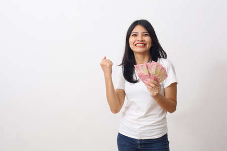 Happy asian girl holds an Indonesian money while standing, looking at camera and clenched her fists. Isolated on white with copyspace Foto de archivo