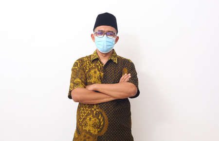 Asian man in batik or Indonesian costume and face mask standing isolated on white background. Concept of charming and positive thinking.