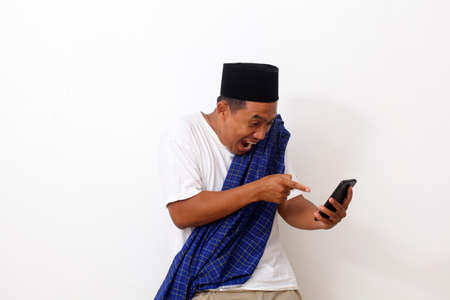 Portrait of happy asian man while standing and holding and pointing on phone cellular. Isolated on white. Ramadan concept Archivio Fotografico