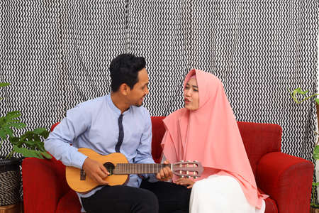 Asian muslim couple sitting on red sofa while playing guitar