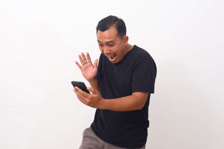 Wow and shocked face of Asian man while looking at his cellular phone. Isolated on white background
