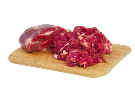 The whole piece and sliced mutton, lying on a wooden board. Isolated on white