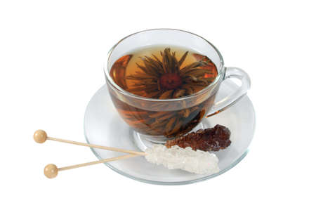 Transparent cup of Chinese tea in the form of decorative flower and two sticks with decorative - white and brown sugar on white background. photo