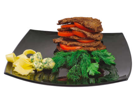 Roast beef on a plate decorated with tomato, isolated on white.
