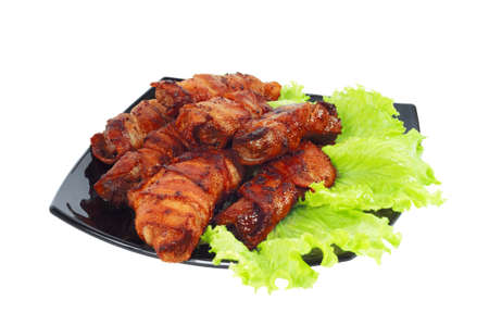 Roasted meat, wrapped in bacon on the dish isolated on white