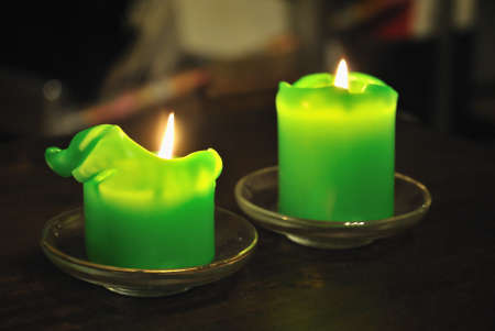 Molten green candle against a dark background. Shallow depth of field. Stock Photo