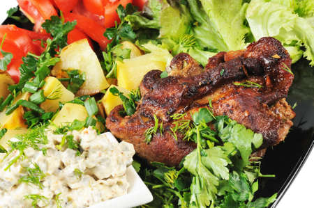 Grilled meat and potatoes. Decorated with tomatoes, lettuce and herbs. photo