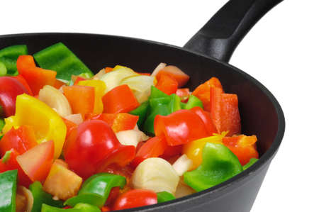 stir fry: Roasting pan with the vegetables. Red and green peppers, onions, tomatoes. Isolated on white